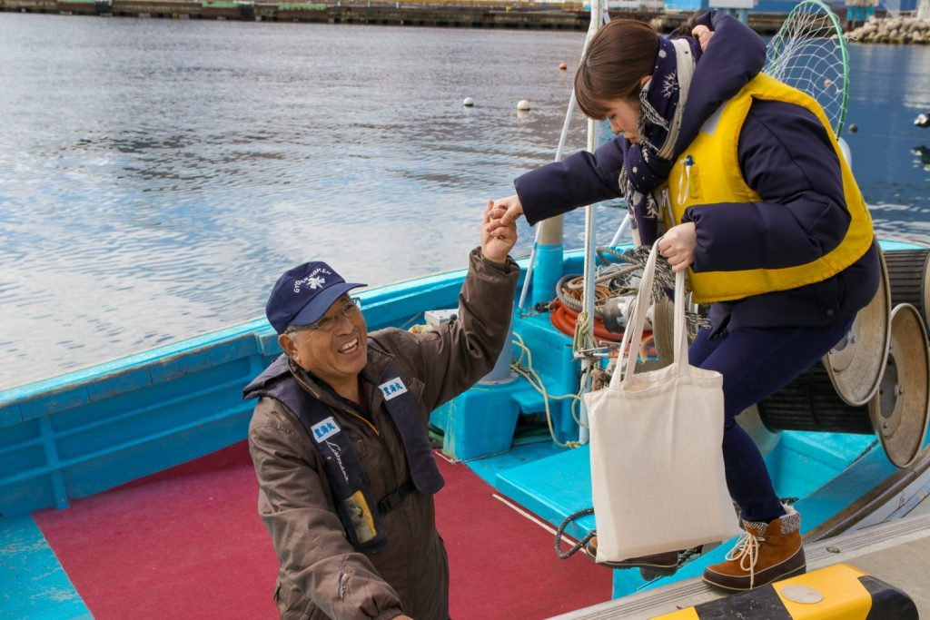 Fisherman helping a girl who is scared of the water get on a boat in Kamaishi City.