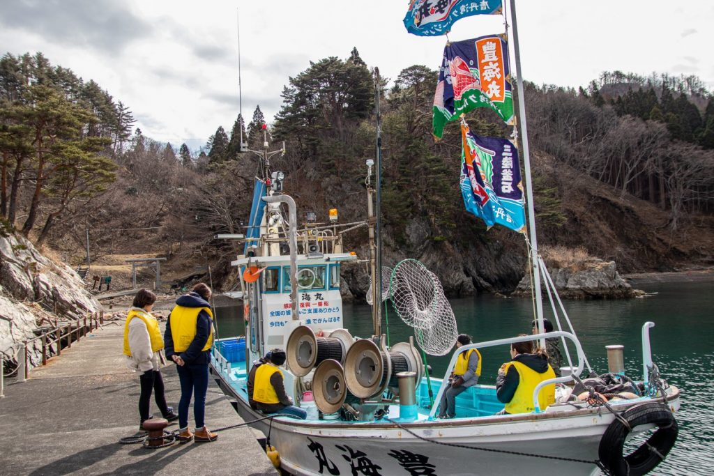 Group of people getting of the boat to walk to Ozaki Shrine in Kamaishi City.