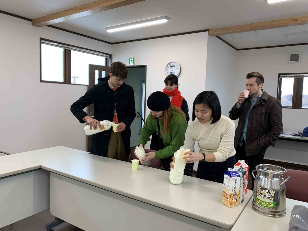 Group of people drinking milk made fresh from Happy Hill Farm in Iwate Town.